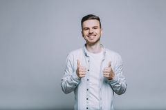 Smiling young man with beard in a white shirt. Handsome smiling young man with beard in a white jeans shirt showing that everything is ok holding two thumbs up Stock Photos