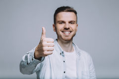 Smiling young man with beard in a white shirt Royalty Free Stock Photo
