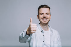 Smiling young man with beard in a white shirt with a thumb up Stock Photos