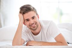 Smiling young man in the bed Royalty Free Stock Photo