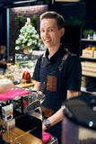 Smiling young man behind the bar Barista prepares coffee and smiles. the cozy atmosphere of the coffee shop stock images