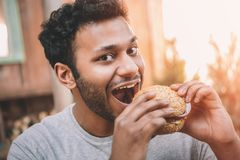 Smiling young man biting fresh hamburger and looking. At camera stock photography