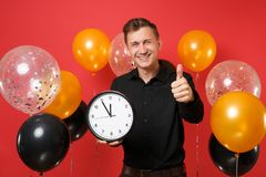 Smiling young man in black classic shirt showing thumb up, holding round clock on bright red background air balloons. St royalty free stock photos