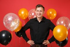 Smiling young man in black classic shirt standing with arms akimbo on bright red background air balloons. Valentine`s. International Women`s Day, Happy New stock photography