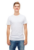 Smiling young man in blank white t-shirt. T-shirt design and people concept - smiling young man in blank white t-shirt Royalty Free Stock Photography