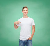 Smiling young man in blank white t-shirt. Gesture, advertising, education, school and people concept - smiling young man in blank white t-shirt pointing finger Royalty Free Stock Image