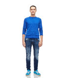 Smiling young man in blue pullover and jeans Royalty Free Stock Photography