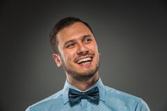 Smiling young man in blue shirt and butterfly tie Royalty Free Stock Images