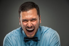 Smiling young man in blue shirt and butterfly tie Stock Photography