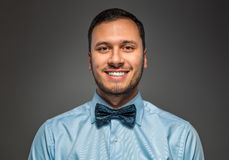 Smiling young man in blue shirt and butterfly tie Royalty Free Stock Photography