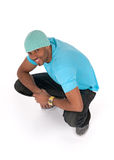 Smiling young man in a blue t-shirt squatting Royalty Free Stock Photos