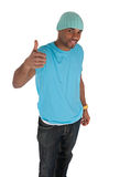 Smiling young man in a blue with thumb up Royalty Free Stock Images