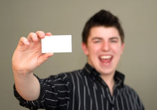 Smiling Young Man with Business Card Royalty Free Stock Image