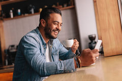 Smiling young man in cafe using mobile phone Royalty Free Stock Photo