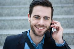 Smiling young man calling by mobile phone Royalty Free Stock Photo
