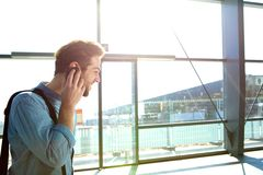 Smiling young man calling by mobile phone at the station Royalty Free Stock Photos
