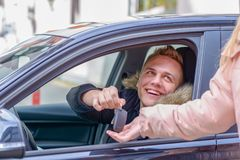 Smiling young man in a car handing over his keys royalty free stock photos