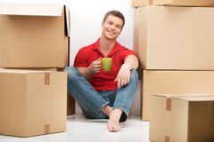 Smiling young man with cardboard box drinking tea. Stock Images