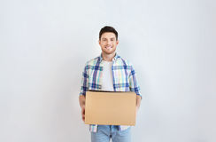 Smiling young man with cardboard box at home Royalty Free Stock Photos