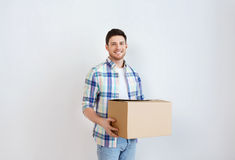 Smiling young man with cardboard box at home Stock Photo