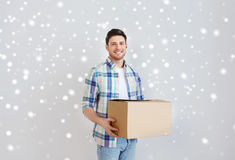Smiling young man with cardboard box at home Stock Images