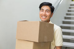 Smiling young man carrying boxes against staircase Royalty Free Stock Photo
