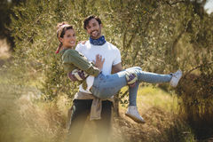 Smiling young man carrying girlfriend by trees at farm Stock Photo