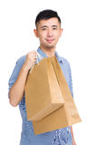 Smiling young man carrying shopping bag Royalty Free Stock Image