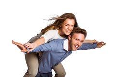 Smiling young man carrying woman Stock Photos