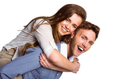 Smiling young man carrying woman Royalty Free Stock Photos