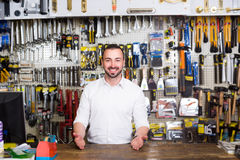 Smiling young man cashier standing at pay desk Stock Photography