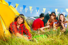 Smiling young man in chaplet sitting near his tent. Portrait of smiling young men in chaplet sitting on the grass near his tent at hippy camping Stock Photos