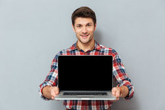 Smiling young man in checkered shirt holding blank screen laptop Stock Image