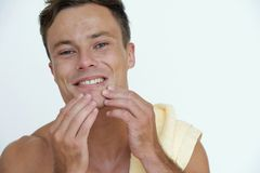 Checking face skin. Smiling young man checking his skin and teeth after taking shower royalty free stock photos
