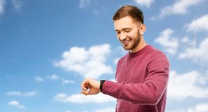 Smiling young man checking time on wristwatch stock image