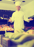 Smiling young man chef deciding on best fruits Royalty Free Stock Photo