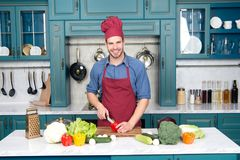 Smiling young man chopping vegetables in kitchen. At home Royalty Free Stock Photo