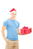 Smiling young man with christmas hat holding a gift and posing. Isolated on white background Stock Images