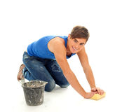 Smiling young man cleaning floor Stock Images
