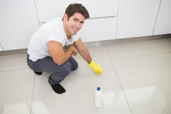 Smiling young man cleaning the kitchen floor Royalty Free Stock Image