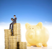 Smiling young man counting coin in piggy bank Stock Photos