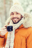 Smiling young man with cup in winter forest Stock Images