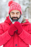Smiling young man with cup in winter forest Stock Photography