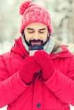 Smiling young man with cup in winter forest Royalty Free Stock Photography