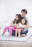 Smiling young man with daughters sitting in his lap at home Royalty Free Stock Photo