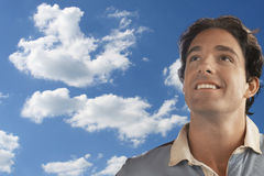 Smiling young man daydreaming against cloudy sky Royalty Free Stock Photos