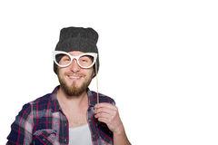 Smiling young man with decorative glasses isolated. Smiling young man with a beard wearing in a plaid shirt and hat with decorative glasses isolated on white Stock Images