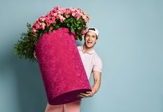 Portrait of happy smiling man shorts and cap delivery guy holding huge pink box with flowers roses for birthday, meeting