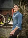 Smiling young man in denim shirt against tree near old train Royalty Free Stock Photo