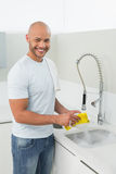 Smiling young man doing the dishes at kitchen sink Royalty Free Stock Photo